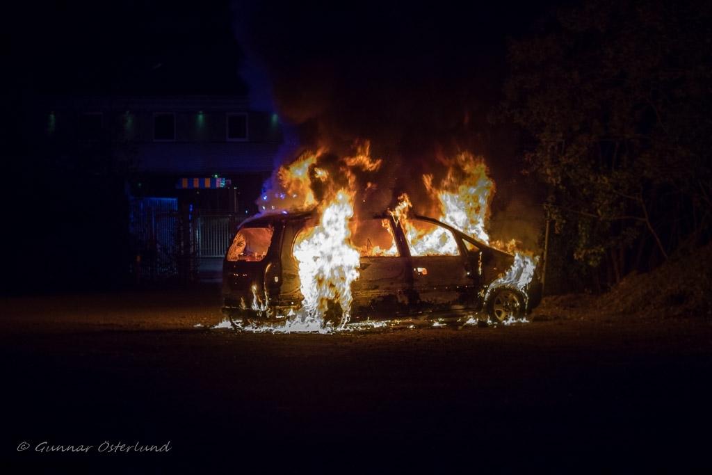 En Opel brinner för fullt på en parkeringsplats.
