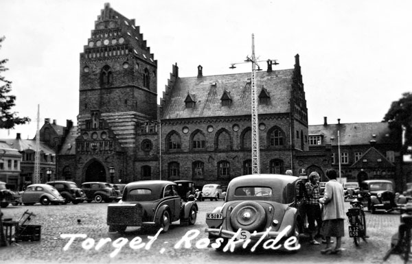 Torget i Roskilde med ett flertal bilar. Minst två från Sverige.