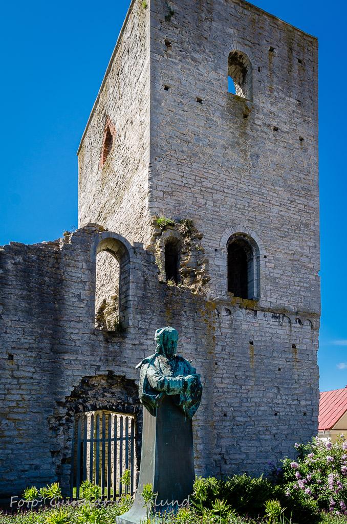 Kristoffer Polhem står staty framför en kyrkoruin.